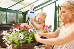 Mother And Daughter Watering Plants In Greenhouse Stock Photo