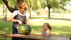 Mother and daughter with watermelon. In park stock footage