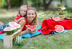 Mother and daughter with watermelons on picnic Stock Images
