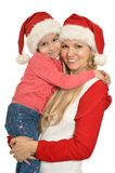 Mother with daughter  wearing Christmas caps Royalty Free Stock Photography