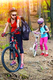 Mother and daughter wearing helmet are cycling on bicycles. Royalty Free Stock Photo
