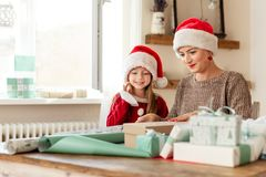 Mother and daughter wearing santa hats having fun wrapping christmas gifts together in living room. Family christmas time. Mother and daughter wearing santa stock photos