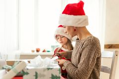 Mother and daughter wearing santa hats having fun wrapping christmas gifts together in living room. Family christmas time. Mother and daughter wearing santa stock images
