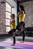 Mother and daughter wearing sports clothing practicing yoga together meditating standing on one leg with hands in prayer stock image