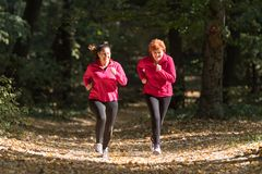 Mother and daughter wearing sportswear and running in forest royalty free stock images