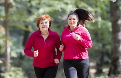 Mother and daughter wearing sportswear and running in forest royalty free stock photos