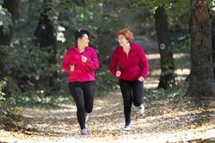 Mother and daughter wearing sportswear and running in forest stock photo