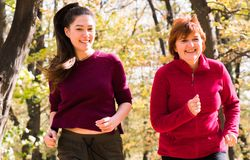 Mother and daughter wearing sportswear and running in forest at mountain stock photos