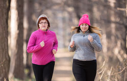Mother and daughter wearing sportswear and running in forest at Royalty Free Stock Photos