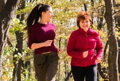 Mother and daughter wearing sportswear and running in forest at mountain stock photo