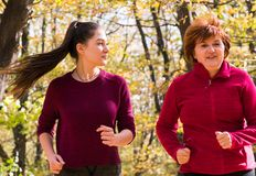 Mother and daughter wearing sportswear and running in forest at mountain stock images