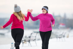 Mother and daughter wearing sportswear and running on snow durin Royalty Free Stock Photo