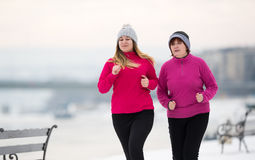 Mother and daughter wearing sportswear and running on snow durin Royalty Free Stock Images