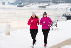 Mother and daughter wearing sportswear and running on snow durin Stock Image
