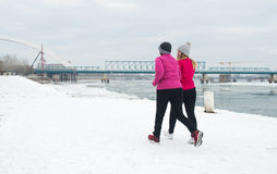 Mother and daughter wearing sportswear and running on snow Royalty Free Stock Image