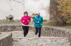 Mother and daughter wearing sportswear and running upstairs at c Royalty Free Stock Photography
