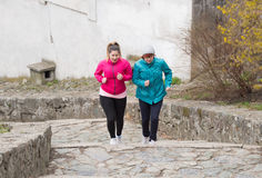Mother and daughter wearing sportswear and running upstairs at c Royalty Free Stock Photos