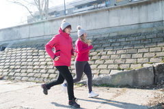 Mother and daughter wearing sportswear and running on windy day. At quay Royalty Free Stock Photo