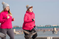Mother and daughter wearing sportswear and running on windy day. At quay Stock Image