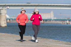 Mother and daughter wearing sportswear and running on windy day. At quay Stock Photo