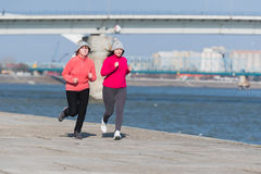 Mother and daughter wearing sportswear and running on windy day Stock Image