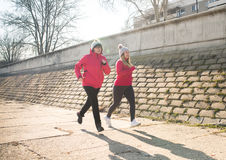 Mother and daughter wearing sportswear and running on windy day Royalty Free Stock Images