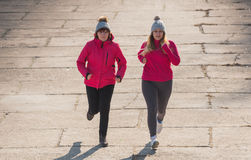 Mother and daughter wearing sportswear and running on windy day Stock Photos