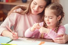 Mother and daughter weekend together at home education concept sitting at the table hugging drawing stock photography