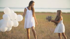 Mom with daughter and balloons. Mother with daughter and white balloons in nature stock video