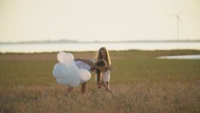 Mom with daughter and balloons. Mother with daughter and white balloons in nature stock footage
