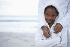 Mother and daughter (8-10) in white clothing standing on beach, smiling, front view, portrait Stock Photos
