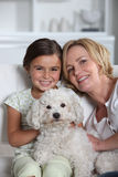 Mother, daughter and white dog Stock Image