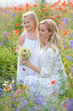 Mother and daughter in white dresses among the flowering meadows Royalty Free Stock Photos