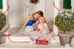 Mother and daughter on a white porch. Stock Photos