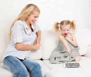 Mother and daughter wiht tablet at sofa Stock Image