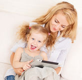 Mother and daughter wiht tablet at sofa Stock Photos