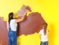 Mother and daughter will brighten the wall with rollers. Repairs in the room royalty free stock images