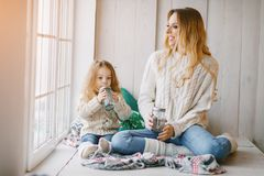 Mother and daughter by the window stock images
