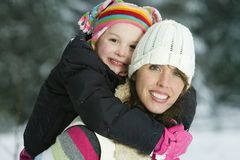 Mother and Daughter in winter. A beautiful women holding a child on her back during a winter snow storm Stock Image