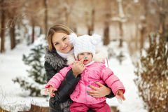 Mother and daughter. Winter gaiety. Mother and daughter outdoors frost. Mother touching her daughter`s nose. Family walk in a winter park. Family happiness royalty free stock photography
