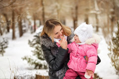 Mother and daughter. Winter hilarity. Mother and daughter outdoors frost. Daughter touches the mother`s nose. Family walk in a winter park. Family happiness Stock Photography
