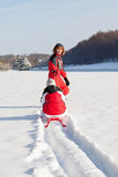 Mother and daughter in winter park. Middle aged women pulling red sledge with her daughter across a snow field Royalty Free Stock Photo