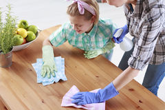 Mother and daughter wiping a table. Mother and daughter wiping a wooden table together Stock Image