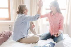 Mother and daughter working together giving high-five stock photography