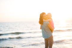 Mother and daughter in workout gear hugging at sunset on beach Royalty Free Stock Photography
