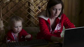 Mother and daughter works on laptop stock footage