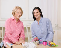 Mother and daughter wrapping gifts together. Adult mother and daughter wrapping gifts together at home Royalty Free Stock Photo