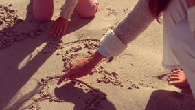 Mother and daughter writing on sand stock video