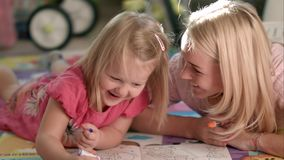 Mother and daughter writing together stock images