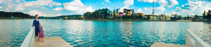 Mother and daughter at Xuan Huong Lake, Dalat, Vietnam. Panorama. Panoramic view of Da Lat city, little Paris of Vietnam. Mother and daughter enjoying at Xuan royalty free stock photography